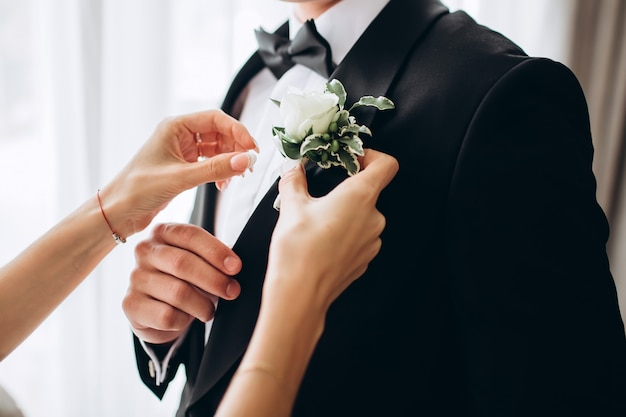 Стильный жених, помогая счастливым женихом, готовящимся утром к свадебной церемонии. роскошный мужчина в костюме в комнате. день свадьбы.