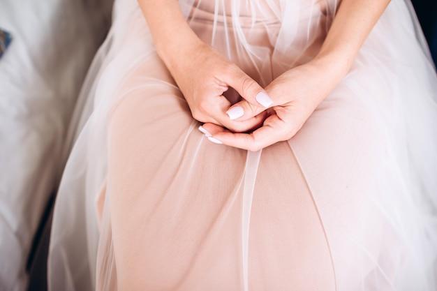白の豪華なドレスを着た豪華な金髪の花嫁が結婚式の準備をしています。朝の準備。ドレスを着ている女性。