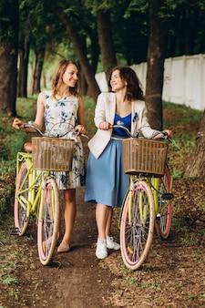 夏の日、路地の公園で自転車で歩いている肯定的で幸せな女の子。自転車で通りを歩いている女性の友人。