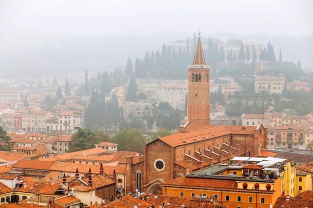 Взгляд на старом городке вероне в виде с воздуха, италии. туман выше в вероне. красные крыши средневекового города в италии