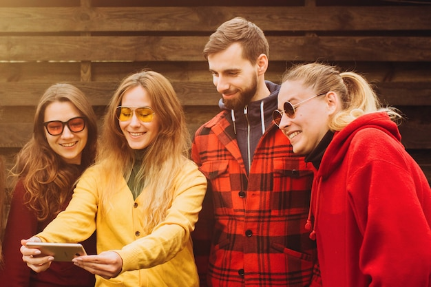 Смешные селфи с друзьями. компания веселых друзей, делающих селфи и улыбающихся, стоя на улице. деревянная стена. люди носят красные и желтые джемперы. молодые люди отдыхают на природе
