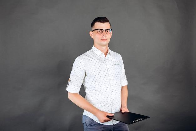 Молодой парень в белой рубашке на темном.