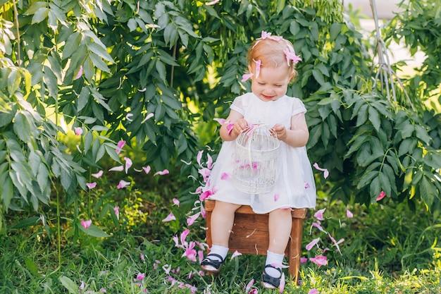 Красивая маленькая девочка со светлыми волосами в белом платье, сидя на стуле в парке солнечный летний день.