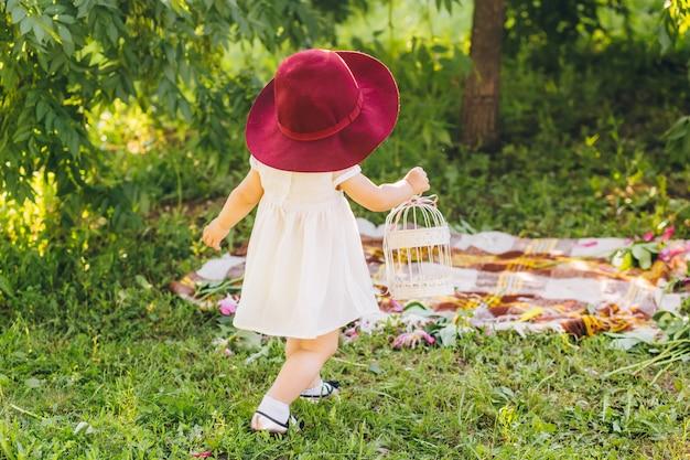 Маленькая девочка со светлыми волосами в белом платье и маминой красной шляпе в парке солнечный летний день