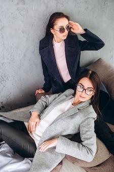 Две молодые девушки сидят на пуфиках в пальто.