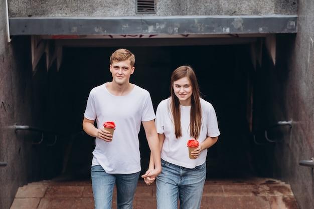 Счастливая молодая пара гуляет по улицам города и пьет кофе из картонной чашки.
