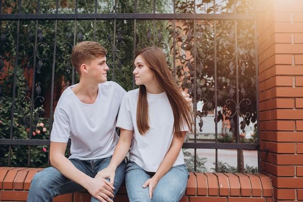 幸せなカップルはレンガの塀に座って笑っています。
