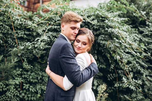 Портрет счастливый муж и жена на фоне зелени.
