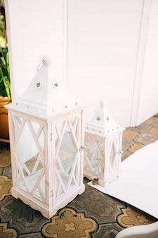 日陰の公園の美しい結婚式の写真ゾーン、白いスクリーン、花と装飾が施された台座。