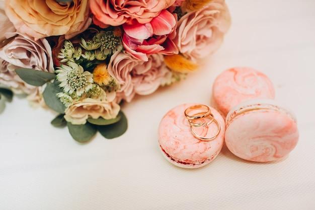 Свадебный букет в осенних тонах, обручальные кольца и миндальное печенье на белом столе.