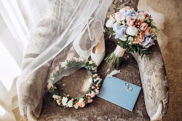 リボン、結婚式の招待状、婚約指輪、椅子に花嫁のための靴でエレガントなウェディングブーケ。