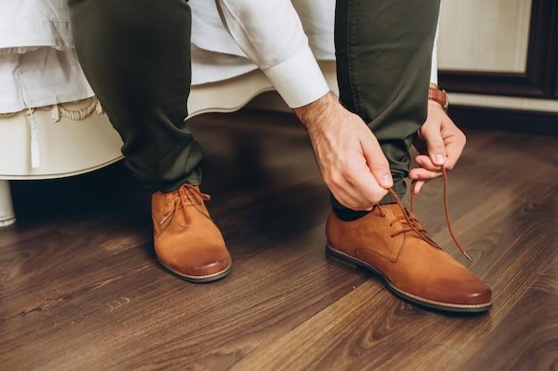 ベッドサイドに靴を履く男性