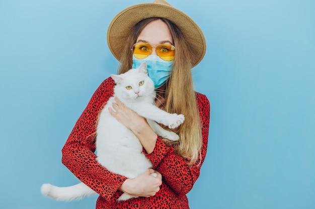 Девушка в платье, шляпу и солнцезащитные очки с медицинской маской на лице. каникулы при эпидемии коронавируса.