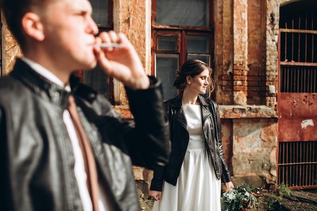 雨の後、若い幸せなカップルが街を歩いています。屋外の革のジャケットで新郎新婦。秋の結婚式。