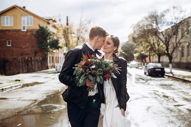 雨の後、若い幸せなカップルが街を歩いています。男と女のクローズアップの肖像画。屋外笑顔の愛情のあるカップル。市内の晴れた秋の日。