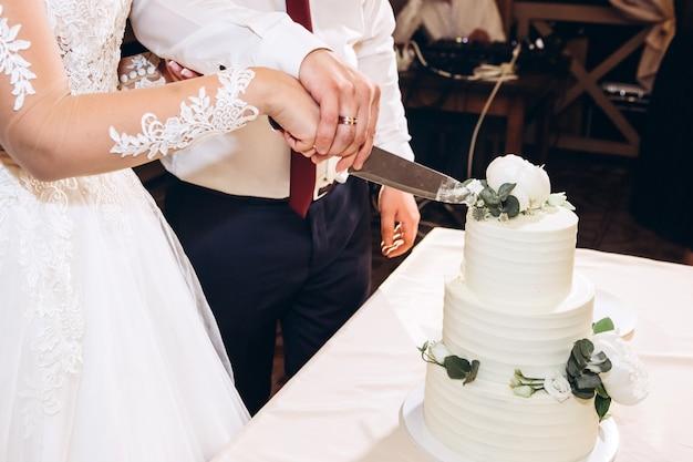結婚披露宴の最後に新郎新婦がウェディングケーキを切りました。若い幸せなカップルは、結婚式の日の終わりにケーキを切った。豪華なウェディングケーキ。