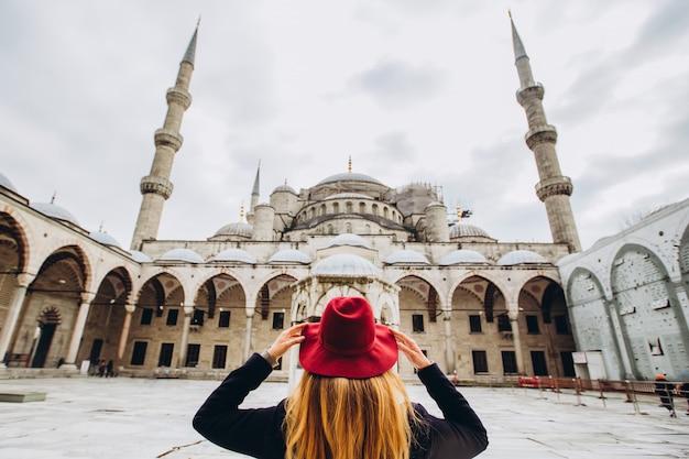 Путешественник молодой женщины в шляпе и черном пальто смотря голубую мечеть в стамбуле, турции. девушка гуляет по зимнему стамбулу. фото путешествия блондинка на фоне мечети в осенний день.