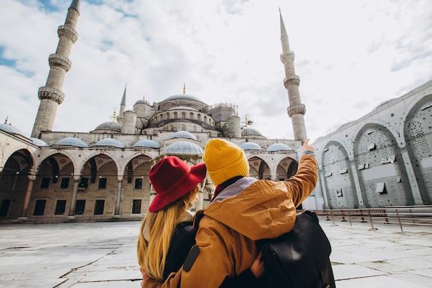 Молодая европейская пара гуляет во дворе голубой мечети в стамбуле, турция. парень и девушка путешественника в желтых шляпах идут в зимний стамбул. пасмурный осенний день в стамбуле.