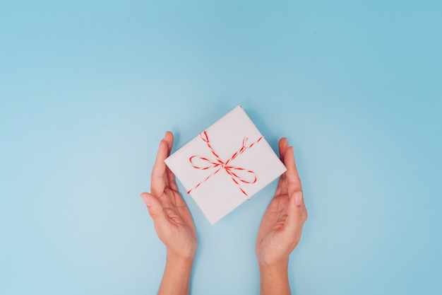 女性の手は青いテーブルの背景、上面にクリスマス、正月、母の日、または記念日のプレゼントとして薄いリボンの白いギフトボックスを持っています。テキストのための場所。
