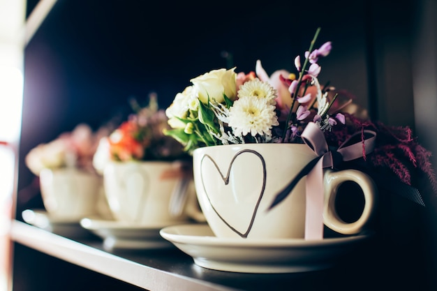 黒い棚の上に花と白いカップ。母の日にバラのカップ。バレンタイン・デー。