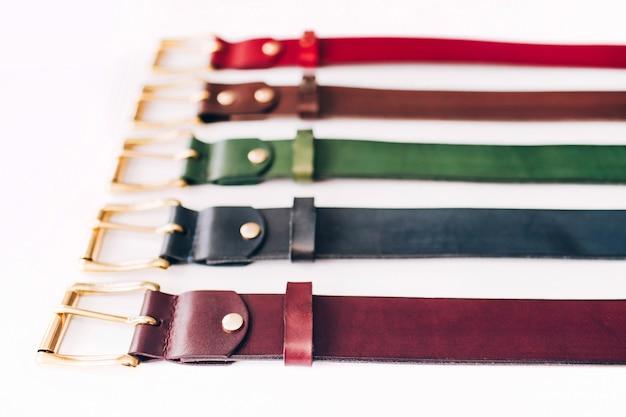 色とりどりのベルト。白い背景の上の革のベルトがたくさん。赤、黄、青、茶、緑の帯が白に刻まれています