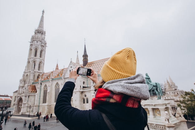 Девушка делает фото на телефон. девушка в желтой зимней шапке взлетает. здание парламента в будапеште.