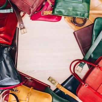 テーブルの上に並べられたカラフルな革のバッグ。バッグを持つテーブルの平面図です。革製品店。革のスーツケースブルー、レッド、イエロー、グリーン。