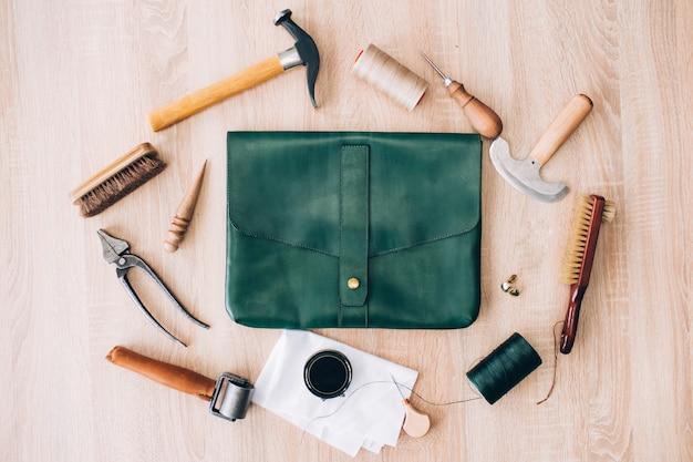 Инструменты для производства кожгалантереи. инструменты разложены на деревянном столе. молоток, кисть, шило, нож, нить, веревка на столе. ручное изготовление кожаных сумок.