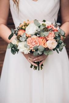Элегантный свадебный букет в руках невесты. букет из оранжевых роз, гвоздики, белого пиона, пионовидной розы. свадебный букет на деревянном