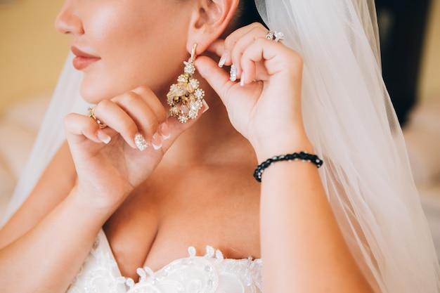 Платья подружки невесты серьги. женщина держит серьгу нежное утро невесты.