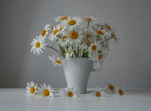 白いテーブルの上のガラスのヒナギク