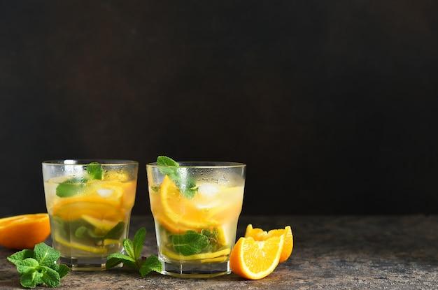 レモン、オレンジ、ミントの冷たいレモネード、コンクリートのテーブル。