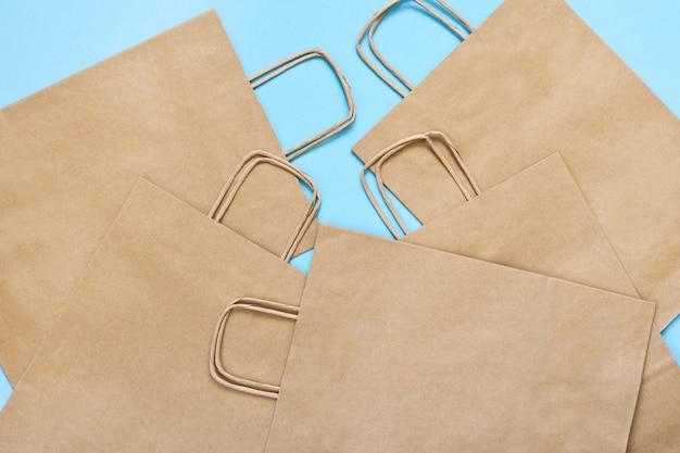 青いテーブルでのショッピングのためのクラフトペーパーバッグのセットです。