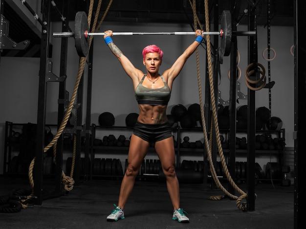ヘビー級の演習を行うジムで筋肉の女性の完全な長さの肖像画
