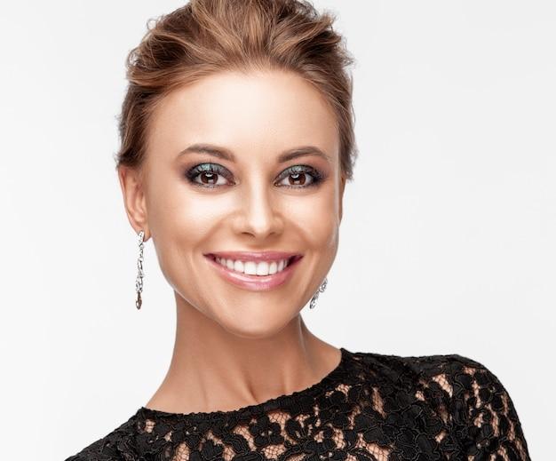 Красивая улыбающаяся женщина с вечерней косметикой. ювелирные изделия и красота. мода фото