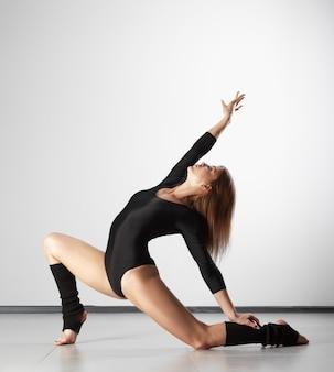 スタジオでポーズをとる若い美しいダンサー