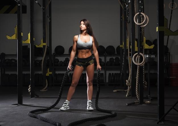 バトルロープで動作するように準備する若い女性