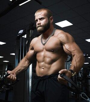上腕三頭筋の演習を行うジムでワークアウト筋肉の男