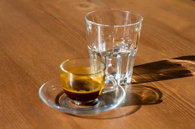 Прозрачная чашка кофейной гущи и пустой стакан стоят на столе. утреннее солнце светит на чашу и стакан, их тени на стол.