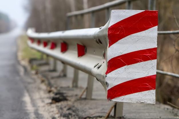 道路に沿って赤い光の反射板が付いた赤白のフェンス