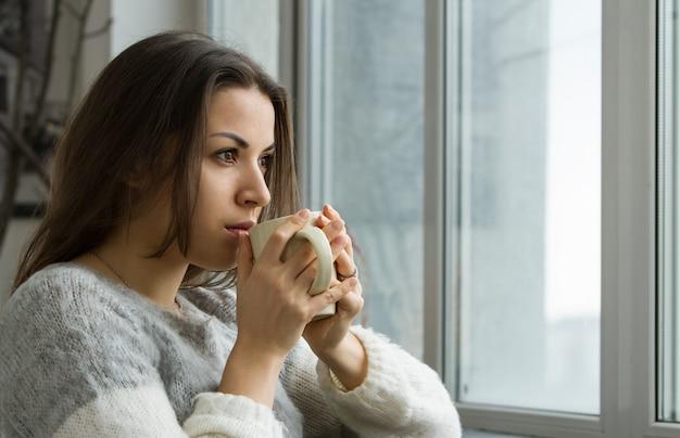 一杯のコーヒーを飲む家の女性
