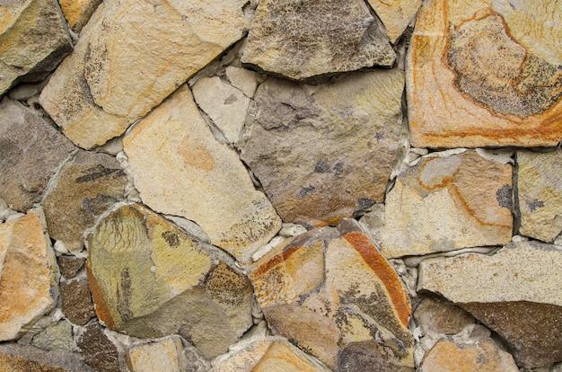 壁には、さまざまなサイズのベージュの玉石がコンクリートで留められています。