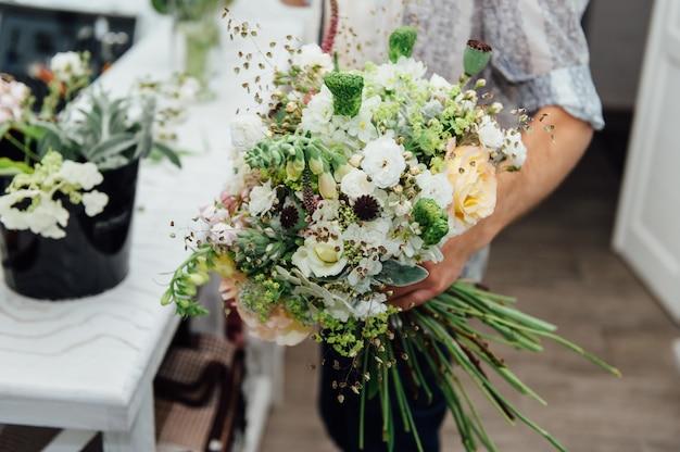 男性の花屋が美しい花束を仕上げ