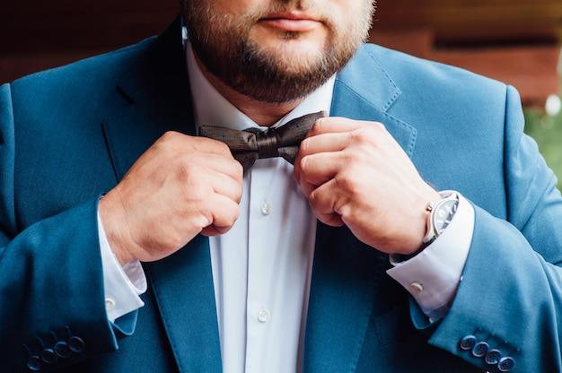 Жених завязывает галстук на белой рубашке