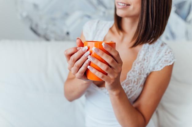 ナイトガウンの美しさの花嫁はコーヒーを飲んでいます。
