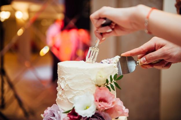 Руки режут вкусный белый свадебный торт
