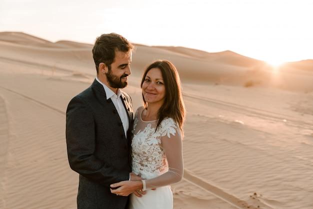 砂漠のウェディングドレスのカップル