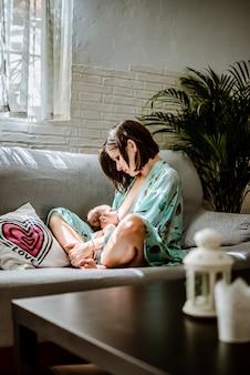 若い女性が彼女の赤ちゃんを自宅で母乳で育てる