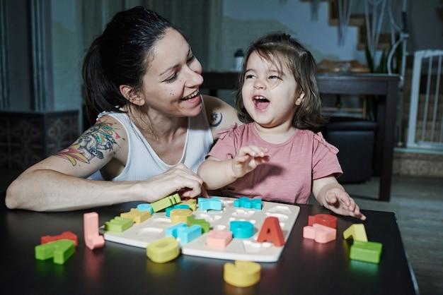 アルファベットの文字を娘に教える母親