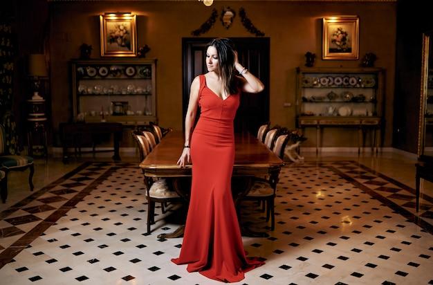 赤いドレスでポーズをとってセクシーな美しい茶色の女性。
